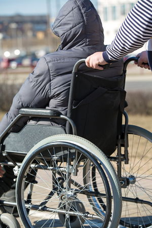 People with limited mobility take a walk with a rollator wheelchair outdoors Stock Photo