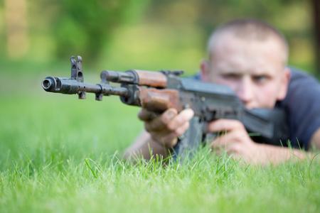 Military man with Kalashnikov rifle took aim outdoors Imagens