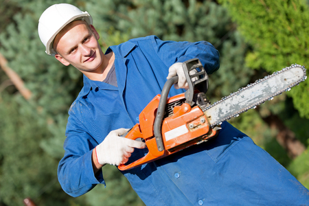 Smiling lumberjack Worker with Chainsaw in Work Wear on Forest background Imagens