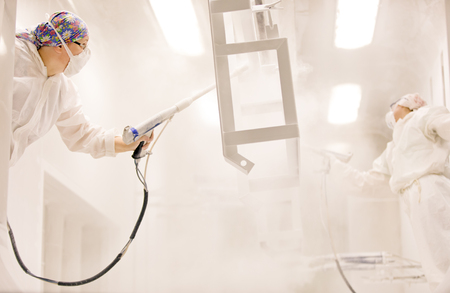 Metal surface finishing: two professional factory painters workers painting metal with guns at manufacture automatic powder coating line