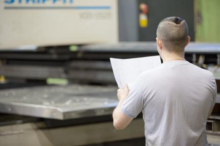 Man worker look engineering drawing blueprints on cnc