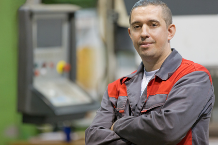 Service man worker with folded arms at factory workshop background