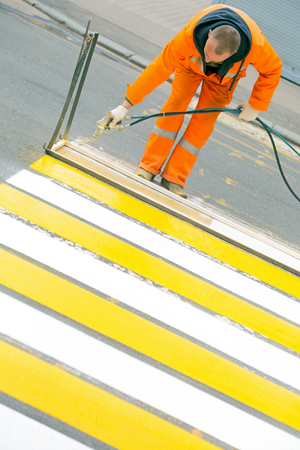 Technical lines man and worker remarking crossing lines on asphalt surface Фото со стока