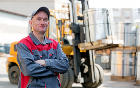Industrial worker on a warehouse forklift truck with a rolled metal steel background