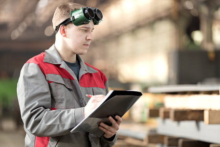 Production man worker with safety glasses writing using clipboard