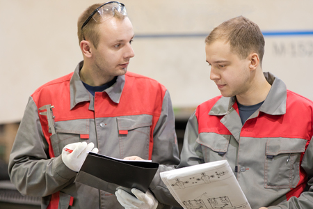 Industrial manufacturing workers with engineering drawing and clipboard