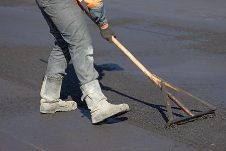 Construction road worker levelling hot mix flexible asphalt concrete pavement