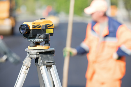 Road works. Land surveying equipment theodolite at construction site on an industrial worker background Imagens