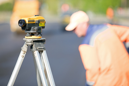 Road works. Land surveying equipment theodolite at construction site on an industrial worker background Stockfoto