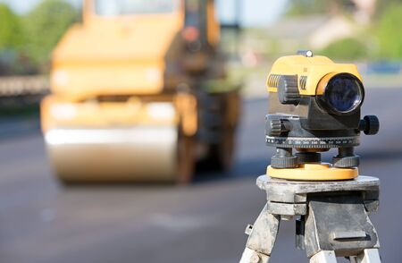 Land surveying equipment theodolite at construction site on road roller machine background during blacktopping works