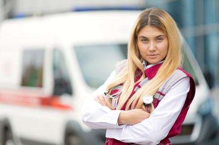 Medical concept.Young paramedic female with phonendoscope at emergency car background