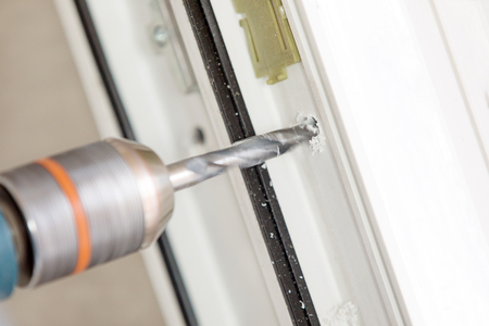 Close up boring hole during PVC window or door installation Imagens