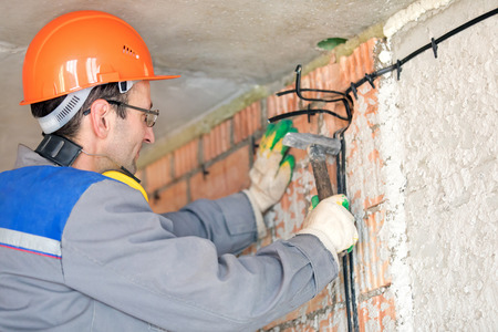 Electrician worker installing cable at house wall