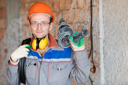 Electrician worker with electrical cable and puncher drill Imagens