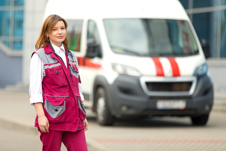 Young paramedic medical technician with phonendoscope at emergency car background Imagens
