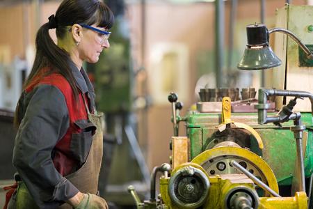 Factory woman turner working at workshop lathe machine