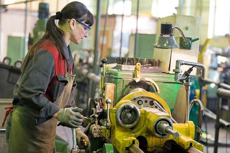 Factory woman turner working on workshop lathe machine