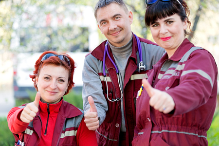 Medical concept. Paramedic response unit gesturing ok at emergency car background
