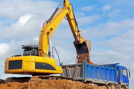 Excavator construction equipment unloading sand into tipper truck