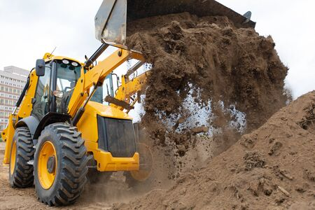 Excavator machine unloading soil sand during earth moving construction works