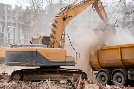 Excavator machine unloading construction garbage from destroyed house into tipper truck Imagens