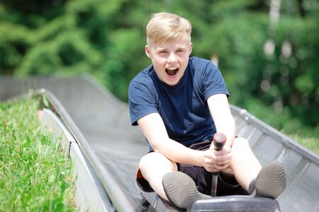 Happy teen boy riding at bobsled roller coaster rail track in summer amusement park Stockfoto