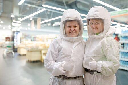 Pandemic virus concept. Two smiling women in protective clothing uniform gesturing OK in supermarket during coronavirus COVID-19 pneumonia outbreak