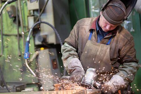 Metalworking industry: factory welder worker grinding steel in workshop with abrasive disc