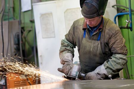 Metalworking industry: factory welder worker grinding steel in workshop with abrasive disk