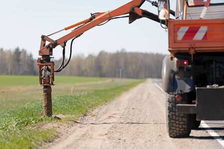 Drilling rig machine boring holes in ground during construction road works Imagens