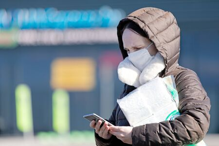 Pandemic virus concept. Woman with medical face mask near supermarket store using the phone to search for internet news