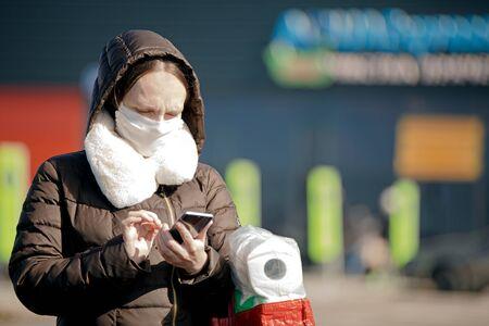 Coronavirus pandemic. Woman with medical face mask near supermarket searching internet news