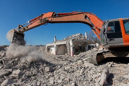 Working excavator digging at construction site during demolition detached house Imagens