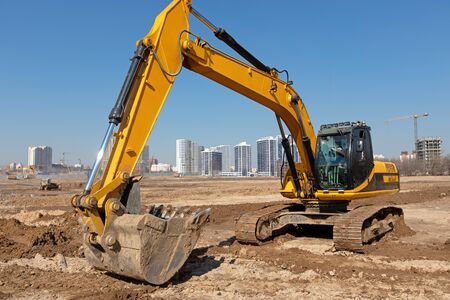 Heavy excavator at construction site with working industrial equipment against urban scene