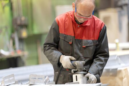 Metalworking industry: factory worker using angle grinder in manufacture workshop