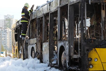 Cal Fire firefighter climbs a ladder by burnt structure public traffic bus