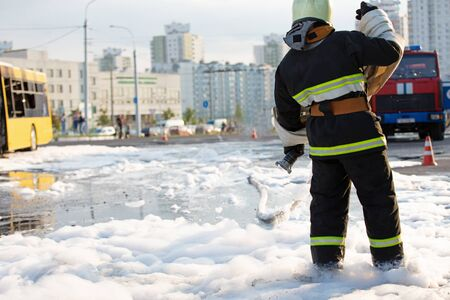 Fireman standing among firefighting foam and carrying fire hose reel after extinguish fire in public transit bus