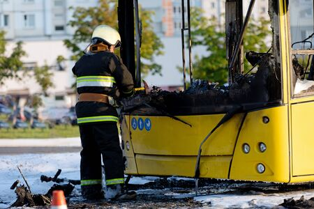 Cal Fire firefighter using axe while extinguish fire that had engulfed entire public transit bus Imagens