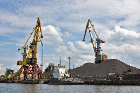 transposition: Bridge cranes at the sea port. Coal transshipment Stock Photo