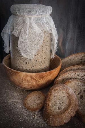 Een heerlijke, goedgezuurde zuurdesem in een glazen pot en naast elkaar geplaatste sneetjes brood. Stockfoto