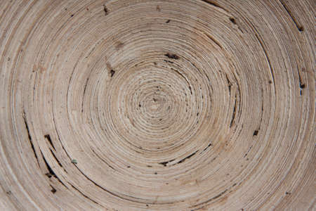 Interior of a wooden bowl with a hypnotizing spiral pattern.