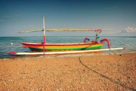 Green colored traditional fishing boat in bali photo