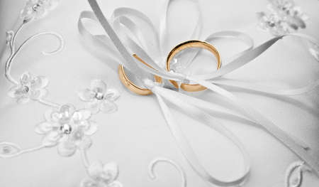 wedding band: two gold wedding rings on a pillow