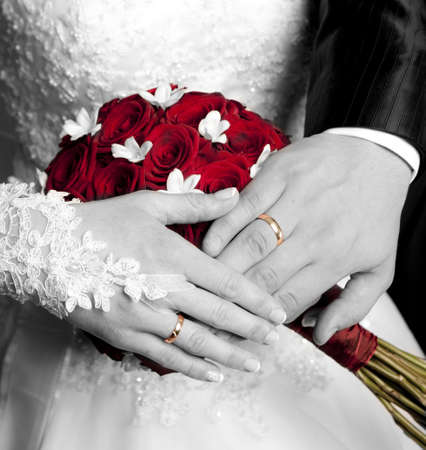 The hands of just married couple on the flowers background photo
