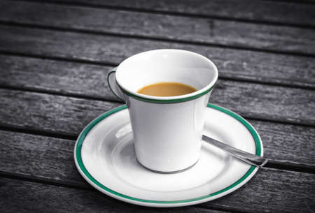 Coffee cup on a wooden table. Dark background. photo