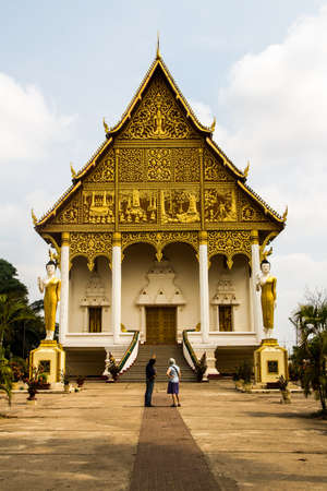 A tour guide explaining the story of Wat That Luang Neua temple to the tourist, Vientiane, Laos