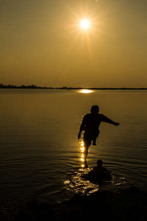 Silhouettes of man who jump off into lake at sunset  photo