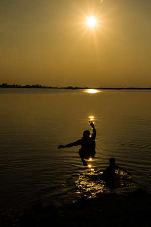 Silhouettes of man who jump off into lake at sunset