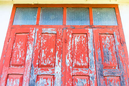 Red wooden window with white wall