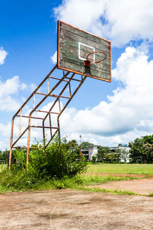 the height of a rim: Old basketball hoop and wooden board on blue sky background